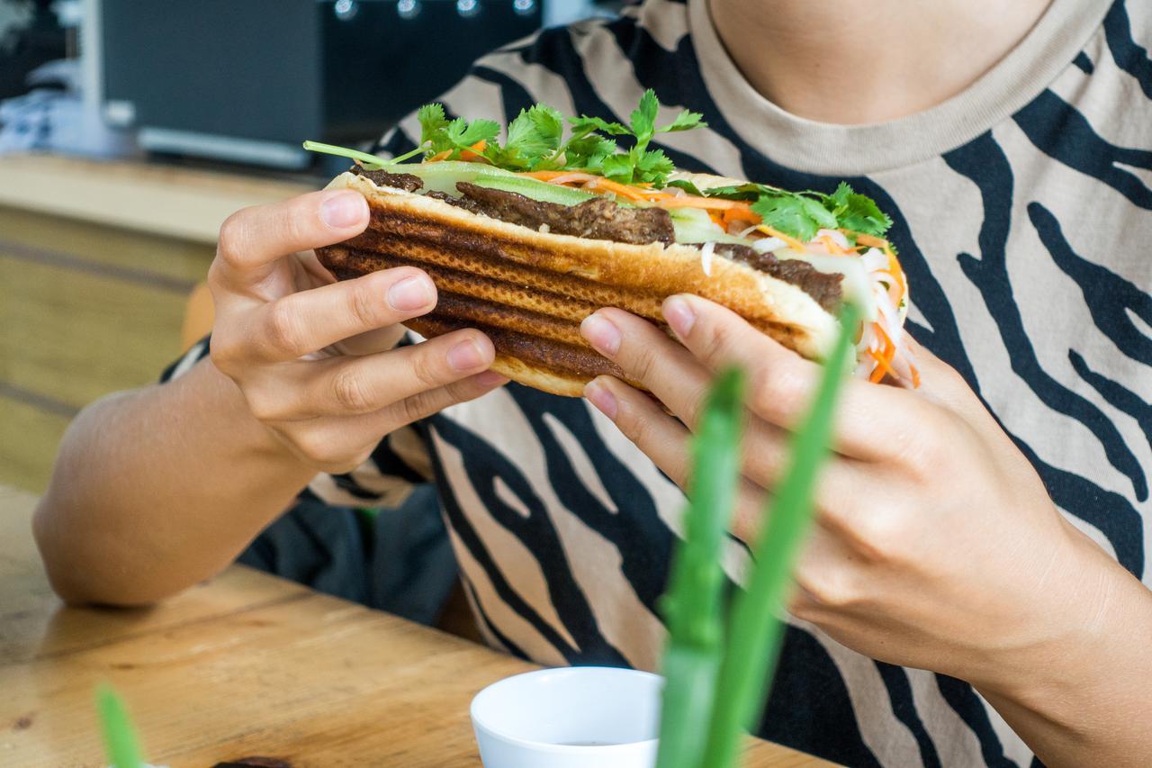 foodiesfeed.com_girl-eating-fresh-vietnamese-baguette-banh-mi.jpg