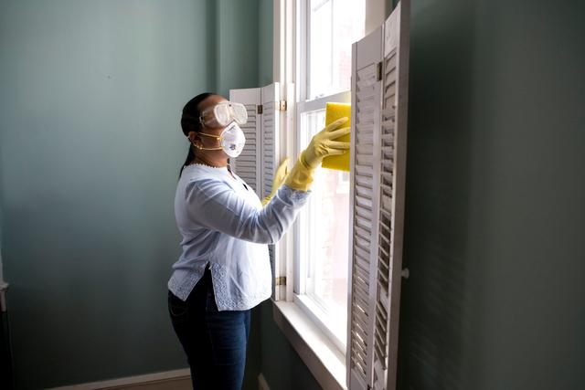 woman cleaning her home before hiring a COVID disinfecting company visits