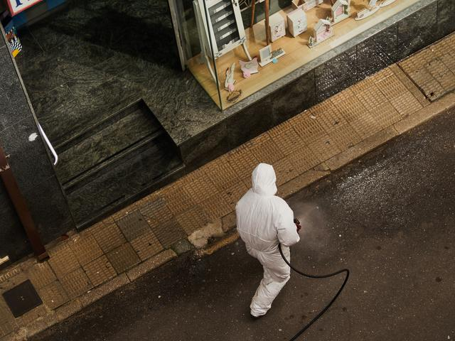 a disinfection specialist conducting a COVID disinfection service on a storefront