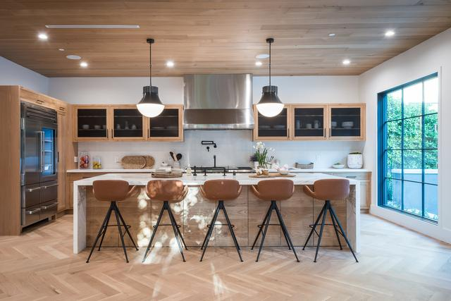 A view of a modern kitchen with barstools at the island, wood flooring, wood cabinets, and a giant window pane permitting sunlight to pour in. Sustainable construction companies sustain your dreams.