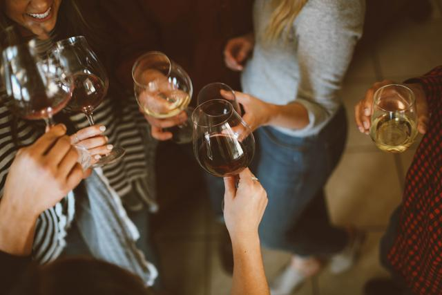 A group of women celebrating by toasting with white and red wine. At twerk classes in Atlanta, working out will feel more like a party.