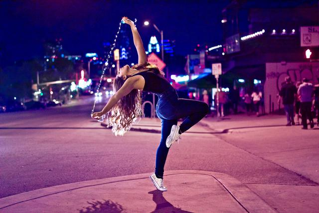 A girl dancing on a sidewalk in a town at night. Hoop classes in Atlanta will make you feel like dancing through the streets.