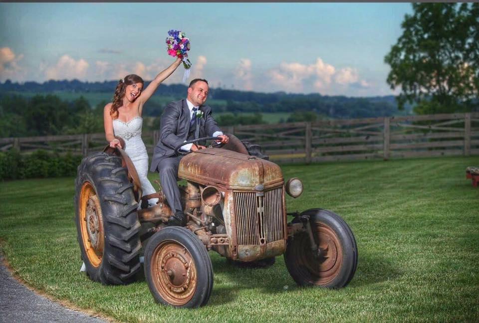 bride and groom riding a tractor at walker's overlook weddinge venue in walkersville, md