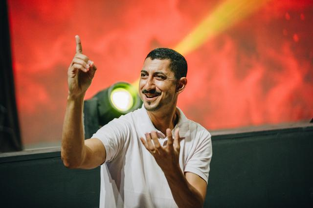 A man with a mustache and white shirt on a stage with a red backdrop using sign language. An ASL interpreter in Miami is indispensable when dealing with people who are hearing impaired.