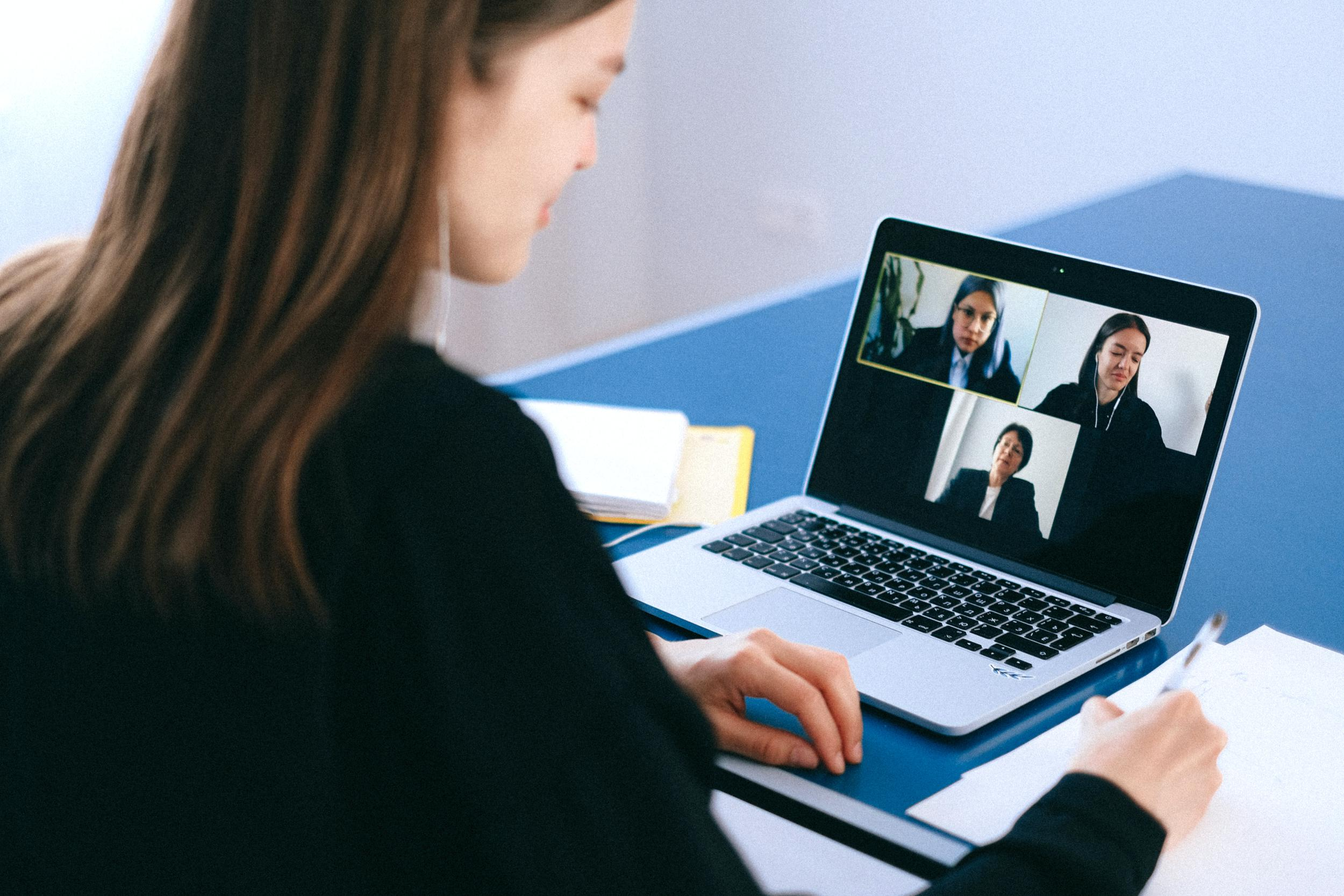 woman with headphones on participating in virtual meeting