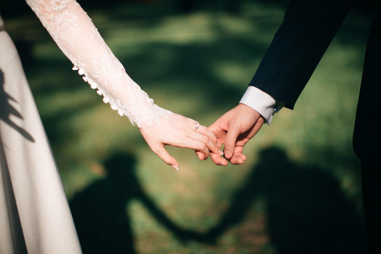 A husband and wife holding hands.