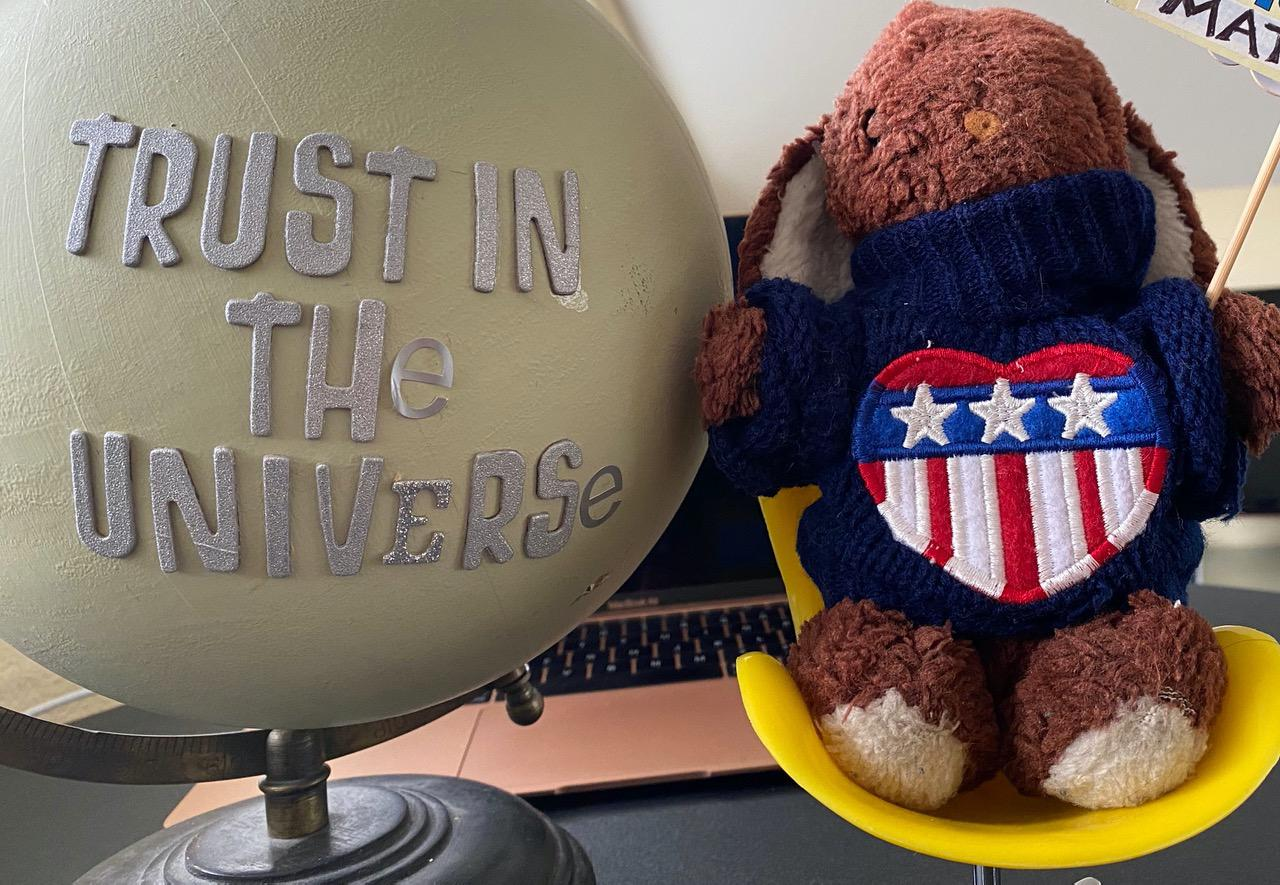 Ms. Bunny stuffed animal and globe that says trus in the universe
