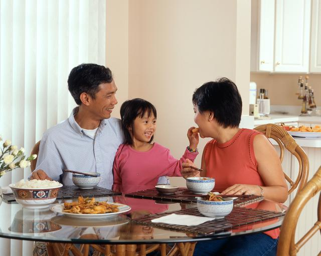 An Asian family, an adult male and female are seated around a table eating a meal with a young female standing in between the adults.