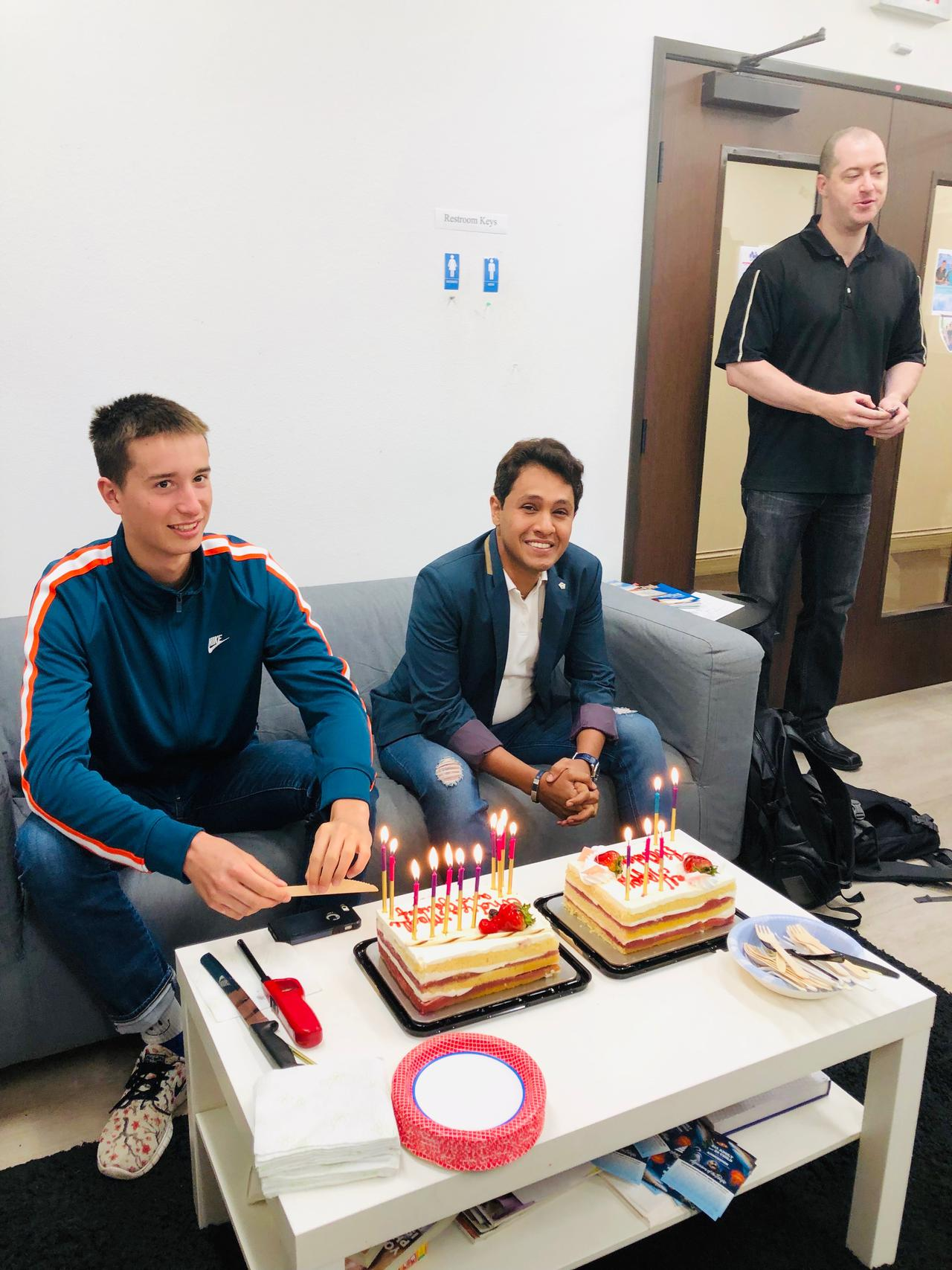 Two happy students on a couch, celebrating their brithday with two cakes in front of them on the table. The best way to understand how to learn English in the USA is through practicing with Americans.