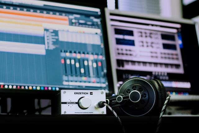 Headphones and headphone amplifier on a desk, monitors with music creation software in the background