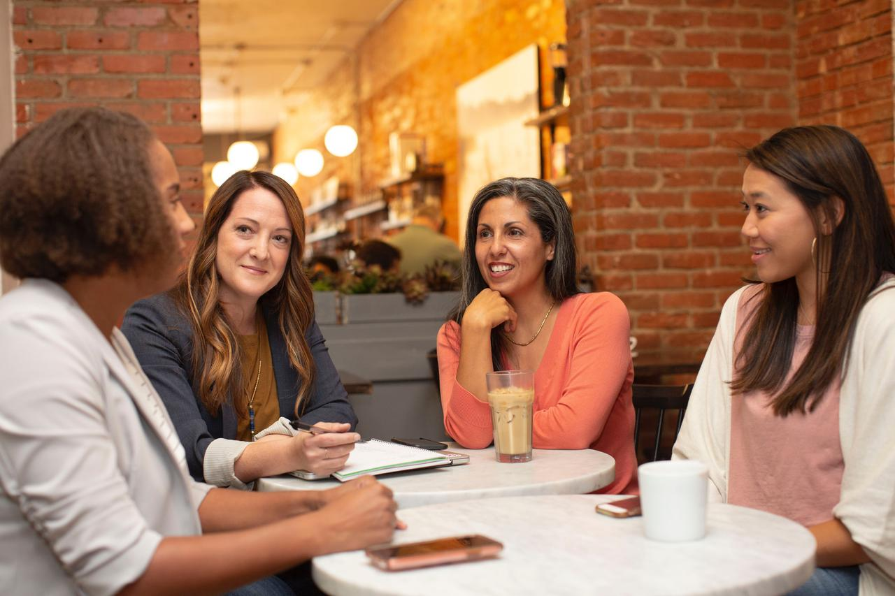Four women working in a business meeting in a cafe coffee shop