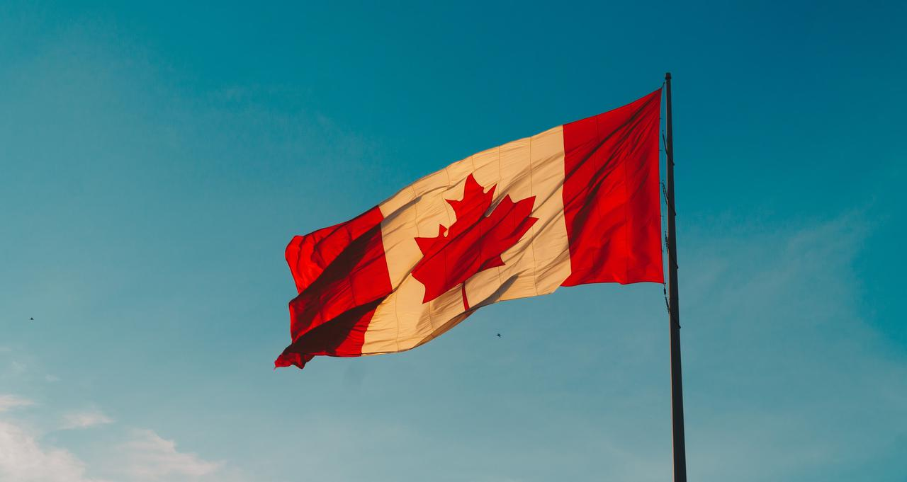 The Canadian flag raised and waving. With a good immigration lawyer in Toronto, you'll feel right at home in Canada.