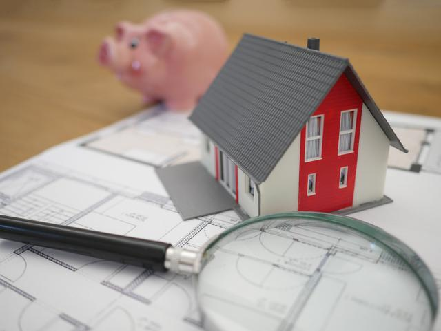 A small model house and a magnifying glass in front of a piggy bank.