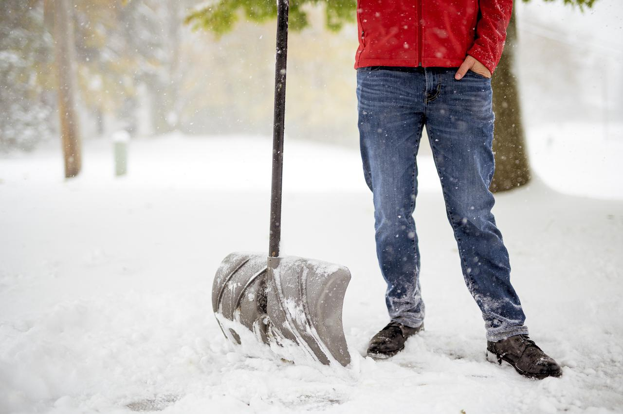 male-standing-on-a-snowy-field-and-holding-a-snow-shovel.jpg