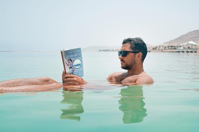 Man in ocean reading backwater.png