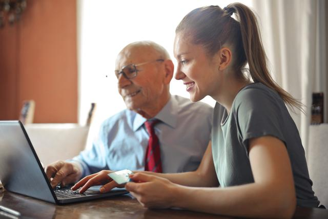 young-woman-helping-senior-man-with-payment-on-internet-3823488.jpg