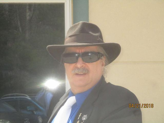 A man in a black hat, sunglasses, and a suit not ready for th photo.