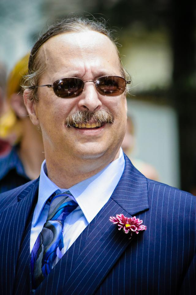 A man with sunglasses and a blue suit smiling.