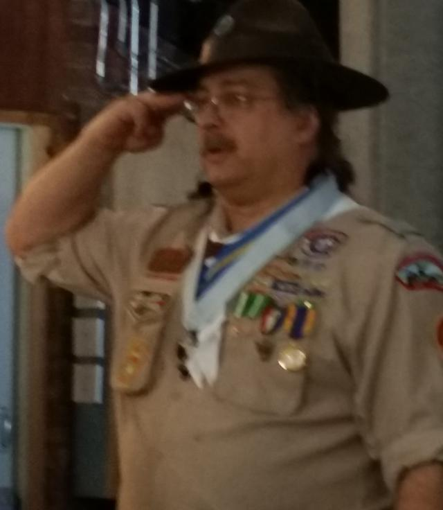 A man in a boy scout uniform standing at attention.