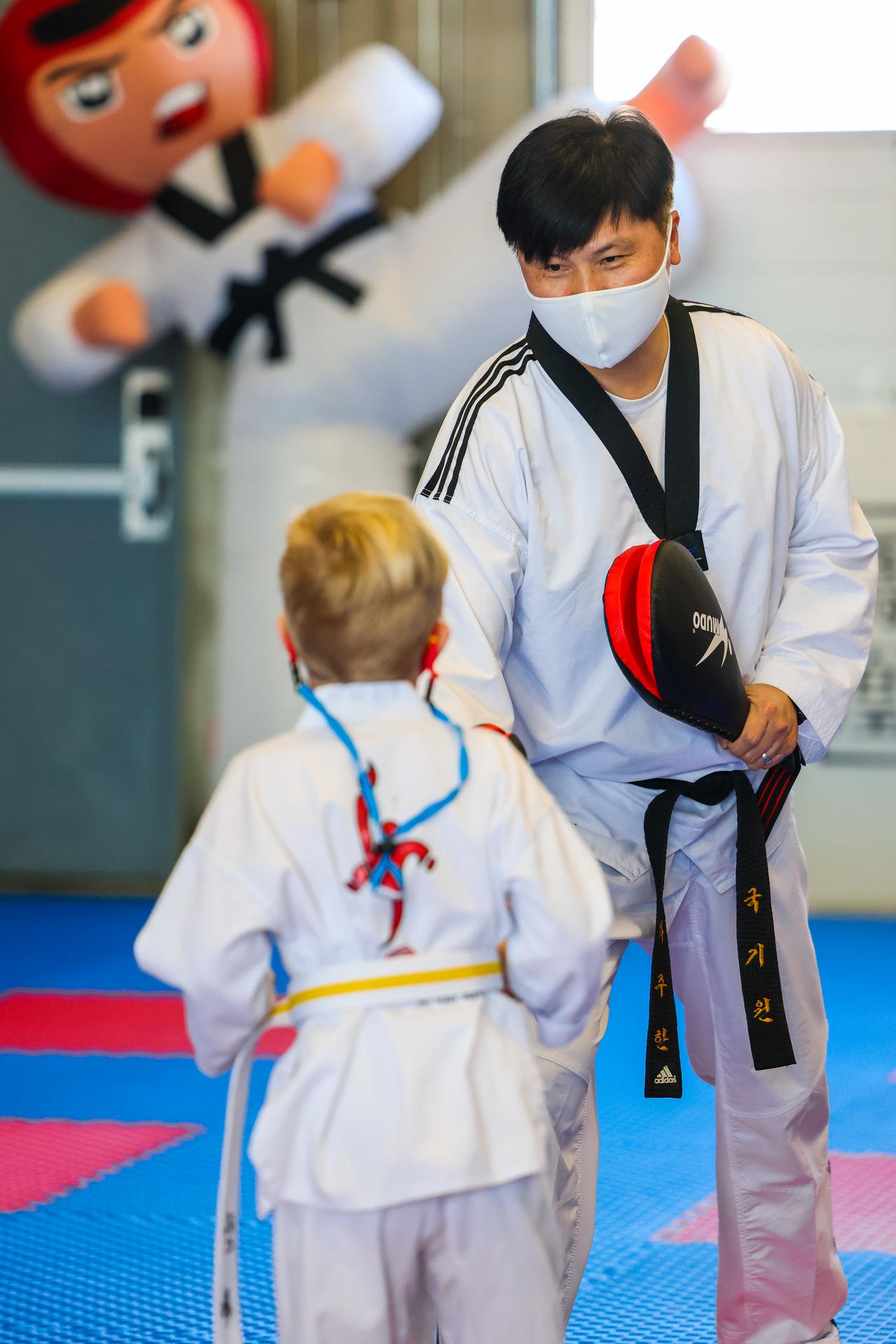 Master Joo-han Cha of Red Phoenix Tae Kwon Do teaching a youth martial arts