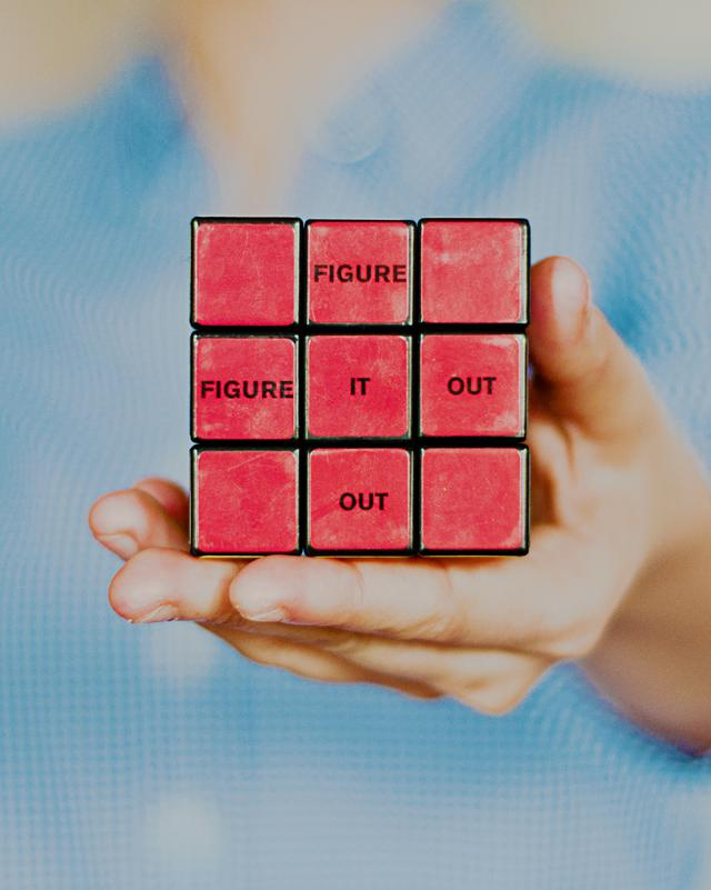 "Person holding a solved rubik's cube with the words ""figure it out""."