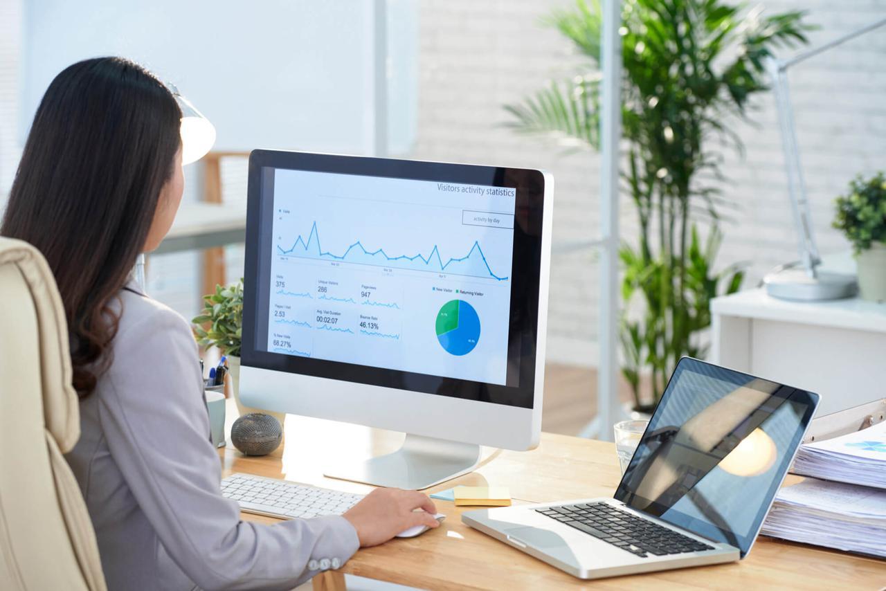 asian-businesswoman-sitting-desk-office-studying-graphs-large-computer-screen (1).jpg