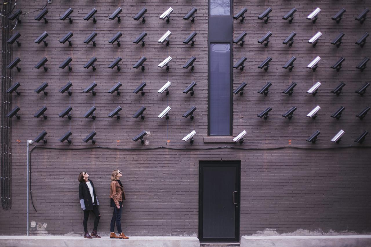 two women standing under security cameras