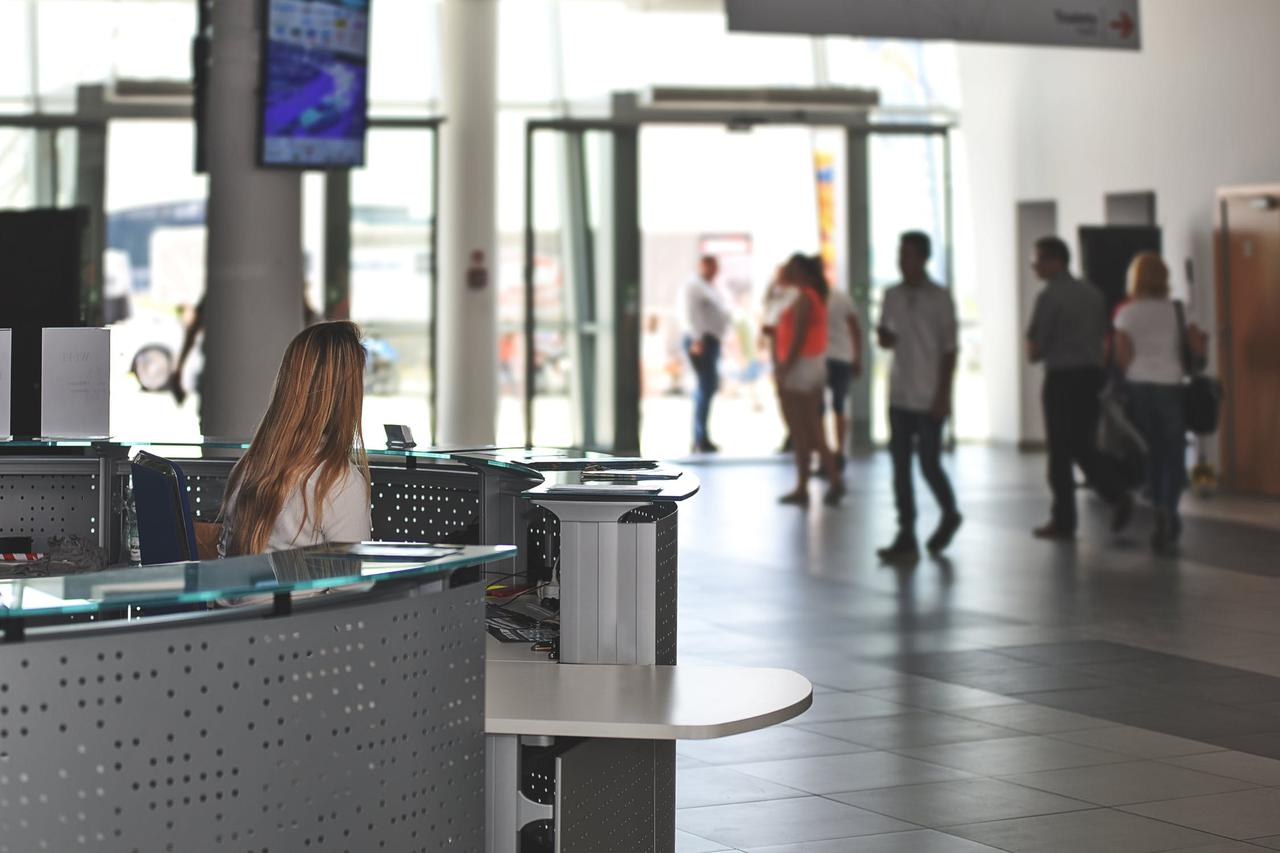 person at desk watching people walk through lobby