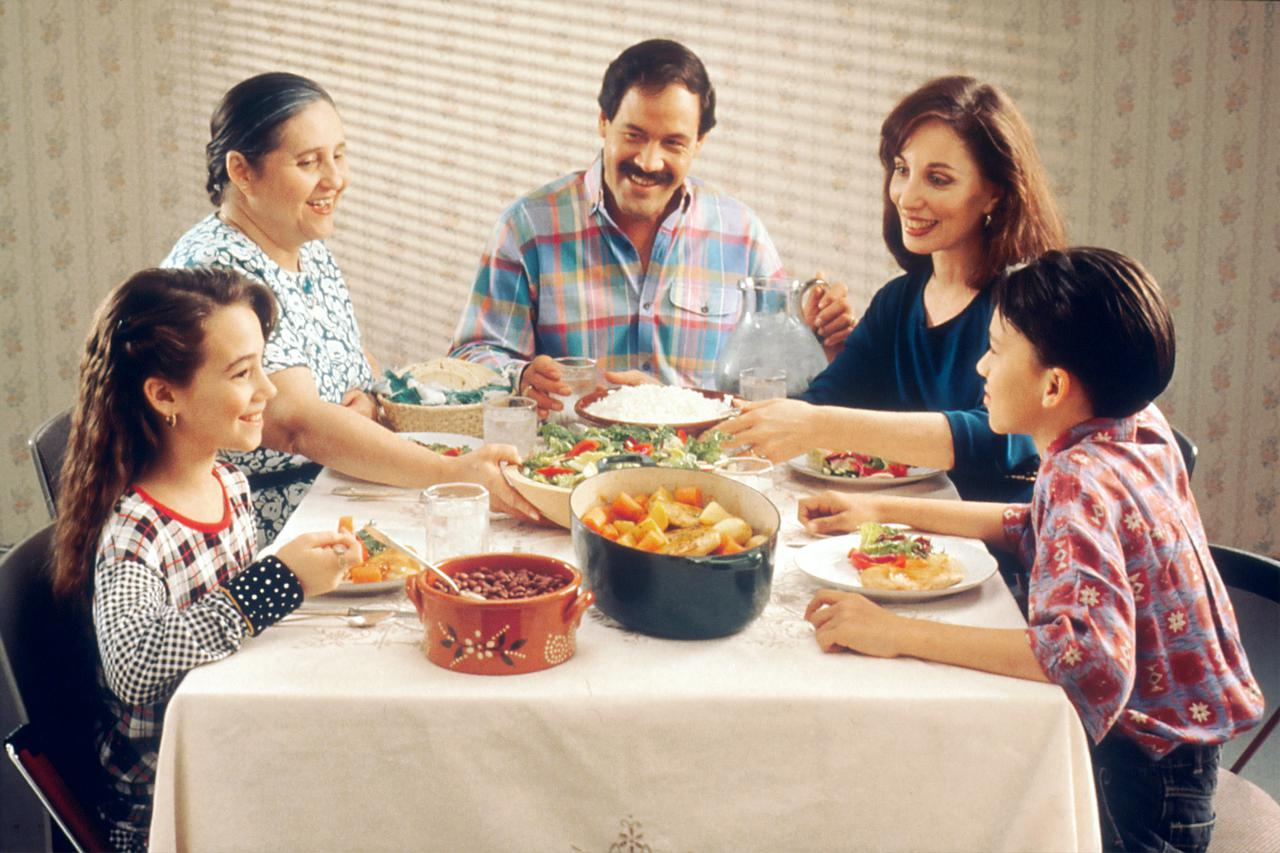 Family Eating Meal. A Hispanic family (male adult, two female adults, female child, and male child) enjoy a meal at the dinner table.