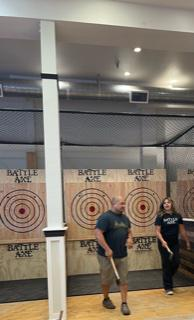 Man and woman standing in front of ax throwing lane.