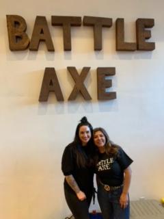 Two women smiling in front of Battle Axe logo.