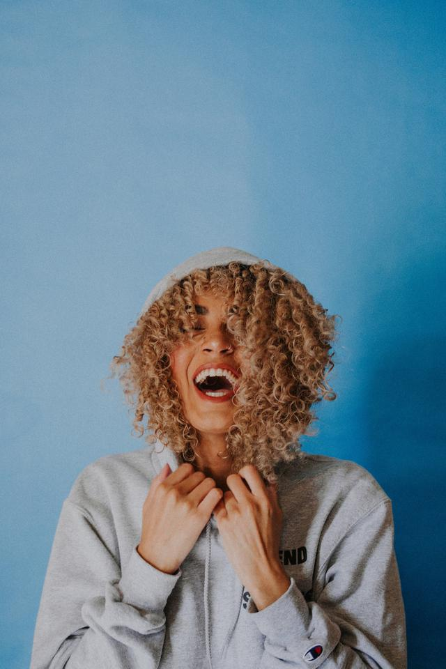 A woman with curly hair and a grey hoodie in front of a blue backdrop. The hood is pulled up and she's laughing. Vaginal rejuvenation in McKinney, TX will make you feel young again.