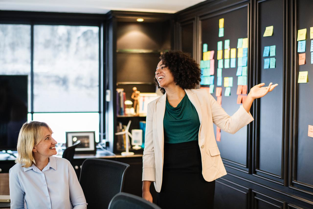 two women interacting in a work environment, symobolizing helping to find jobs for people with disabilities