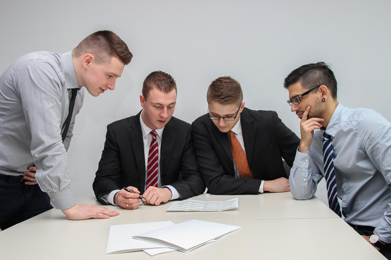 A group of lawyers in suits and ties analyzing a document and discussing it. A Tampa, FL criminal defense attorney is your surest route to redemption.