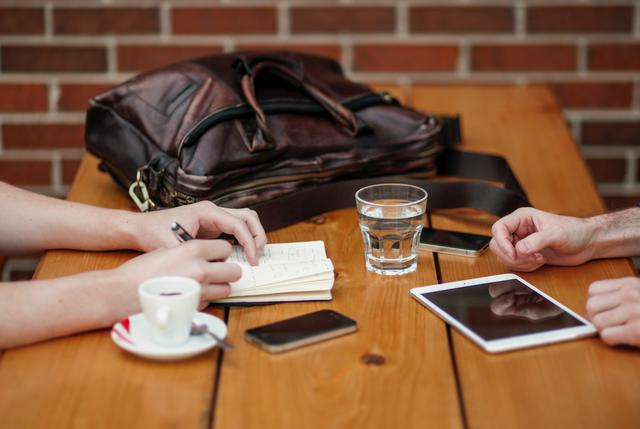 two people meeting with iphone and ipad