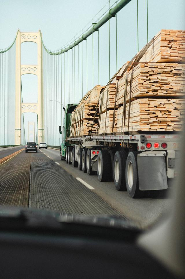 A flat-bed truck transporting wood pallets over a bridge.