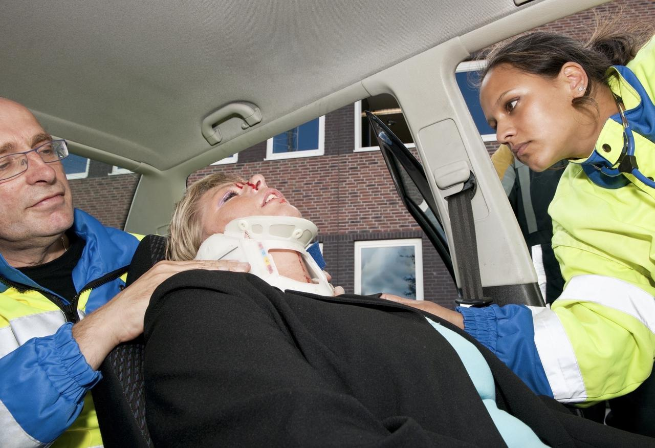 EMTs rescuing a woman injured in a car accident