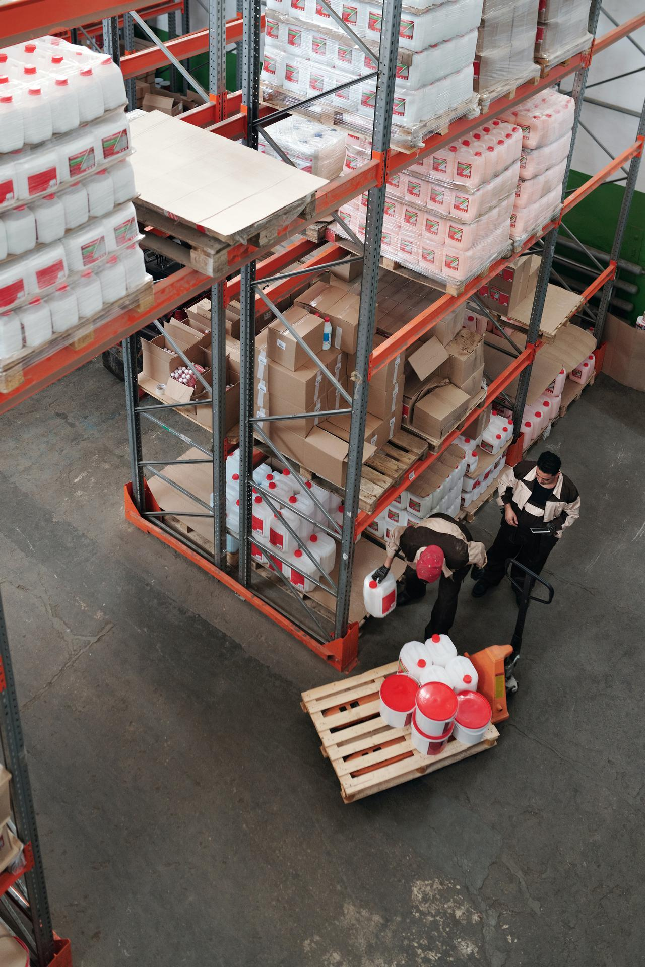 two men moving jugs in a warehouse