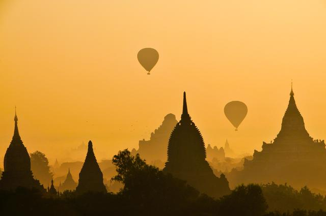 "This photo was one of many taken at the Sunrise Pagoda in December of 2011.This was my first trip to Burma, an eye opening trip for sure. In the ancient capital of Bagan, a small boy saw me early in the morning and said, ""where you are going?"" I said, ""to the sunrise Pagoda…""  He said, ""I take you a shortcut...."" It was a shortcut indeed and after climbing to the second level of this ancient pagoda the light was perfect, the balloons came and viola! I gave my tour guide a small reward for his efforts to get"