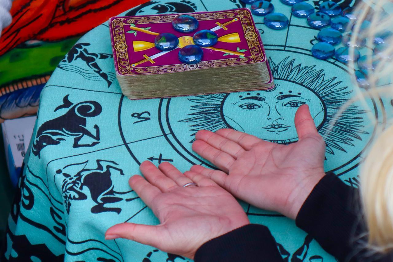 A psychic advisor in Sacramento reading palms and tarot cards.
