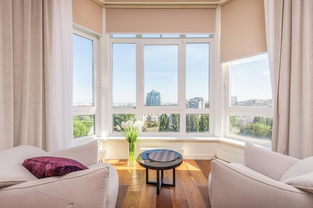 This is a photo of the interior of an apartment, featuring a bay window with a white frame. The image accompanies a blog post on DIY vs. professional window installation.