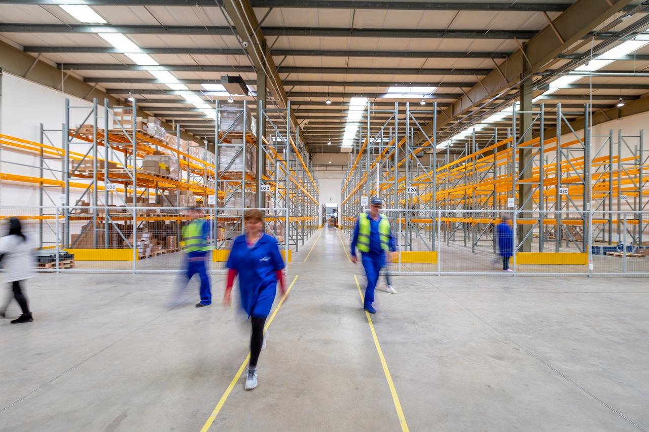 Five warehouse workers walking quickly in different directions.