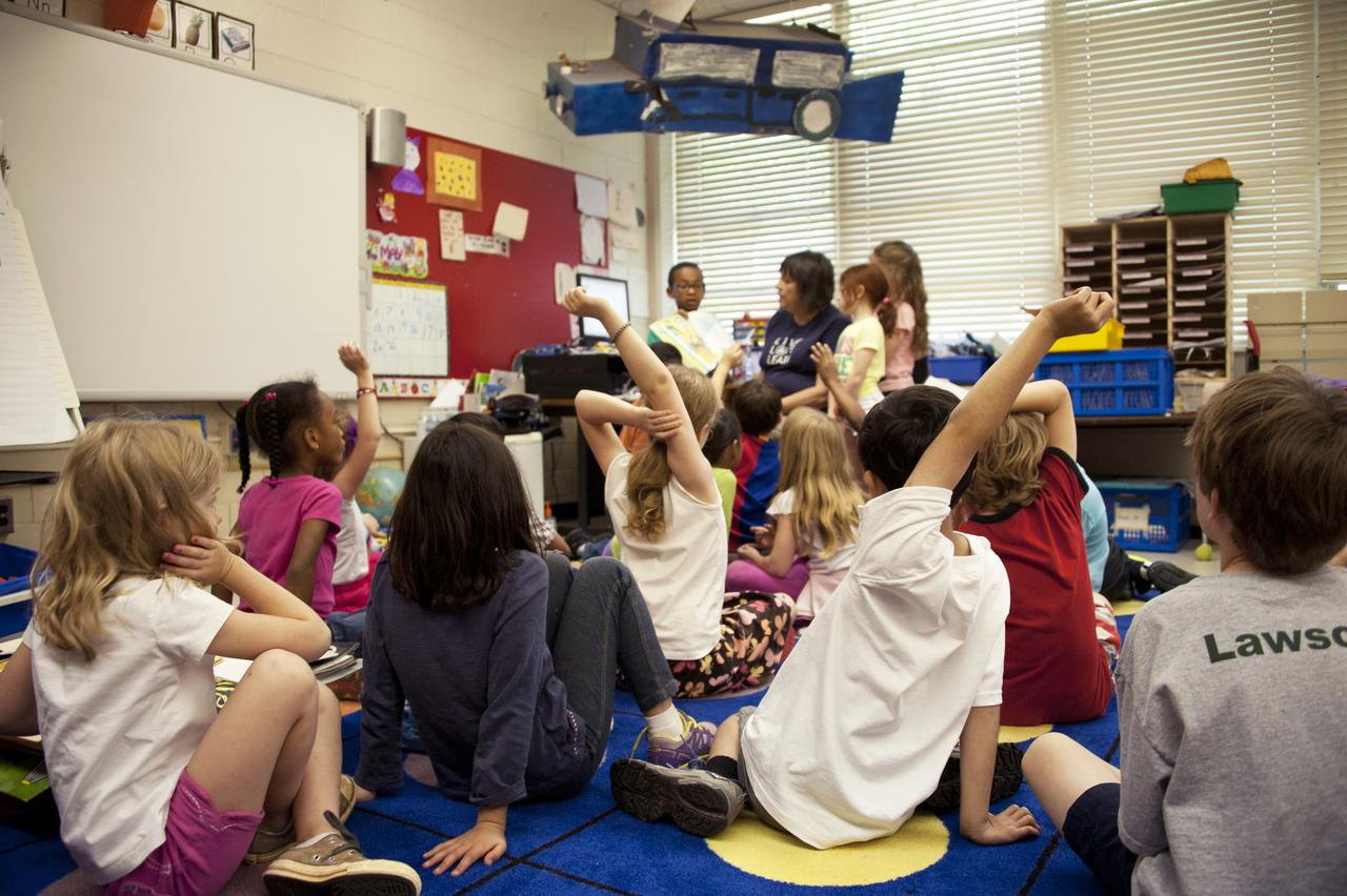 Captured in a metropolitan Atlanta, Georgia primary school, this photograph depicts a typical classroom scene, where an audience of school children were seated on the floor before a teacher at the front of the room, who was reading an illustrated storybook, during one of the scheduled classroom sessions. Assisting the instructor were two female students to her left, and a male student on her right, who was holding up the book, while the seated classmates were raising their hands to answer questions related