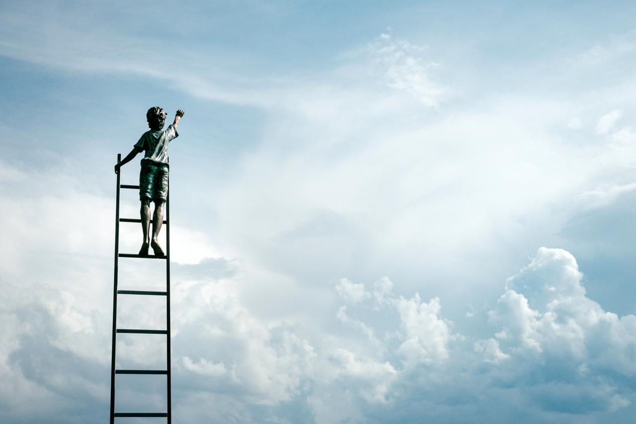 boy standing on ladder reaching for the clouds