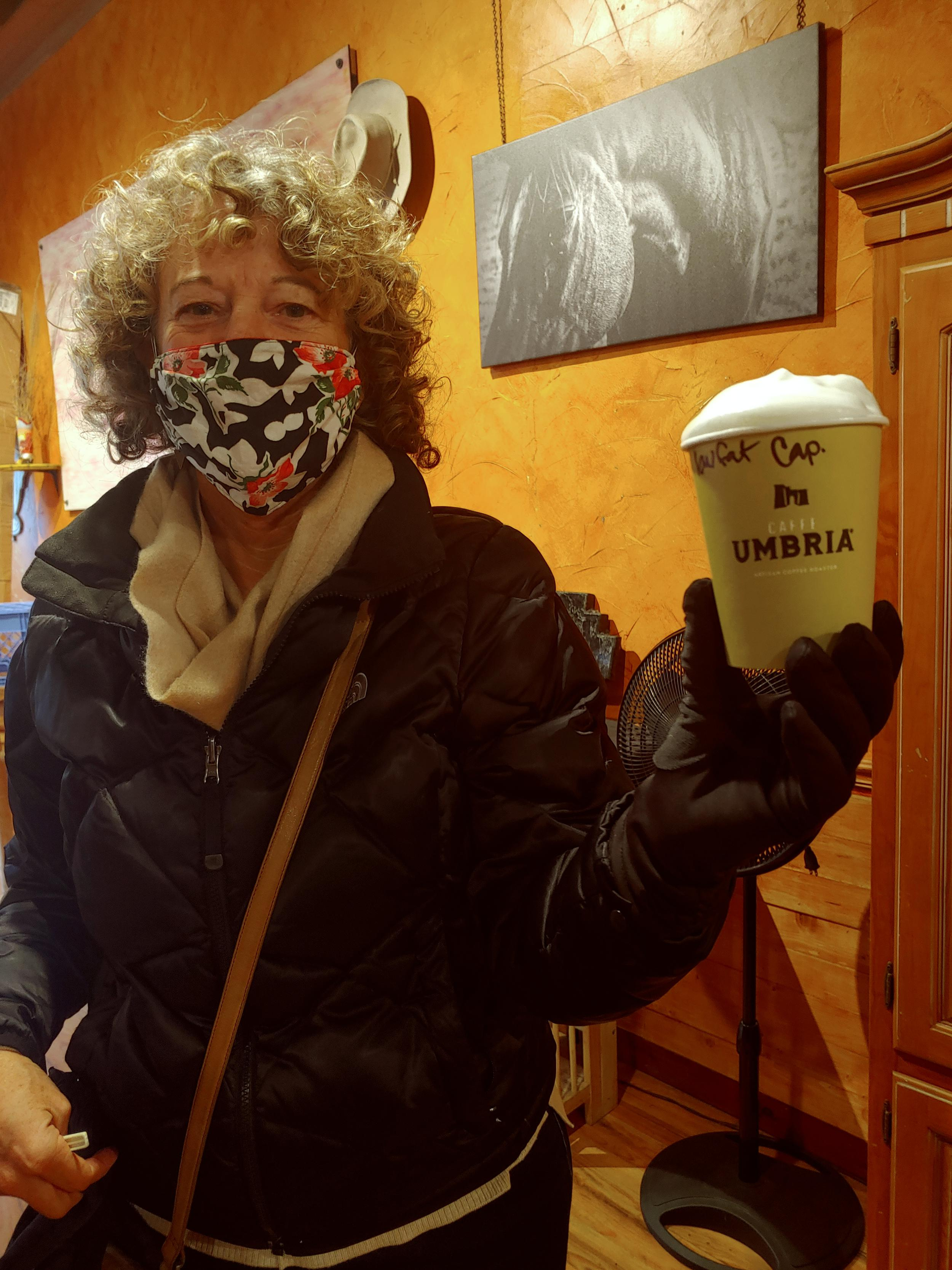 woman in face mask holding a cup of coffee for takeout