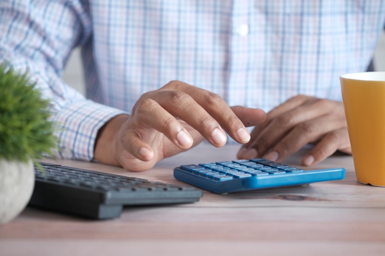 Close up of man hand using calculator.