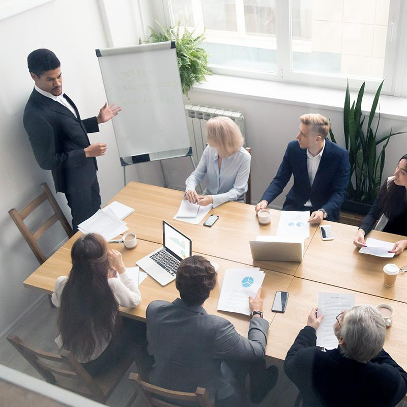 Photo accompanies a description of financial projection services and shows a group of people seated at a conference room table while a man in business attire gives a presentation.