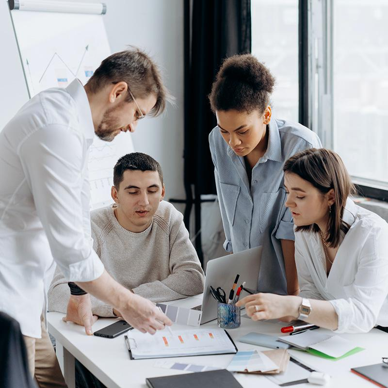 Photo accompanies a description of financial statement preparation and shows four people gathered around a laptop.