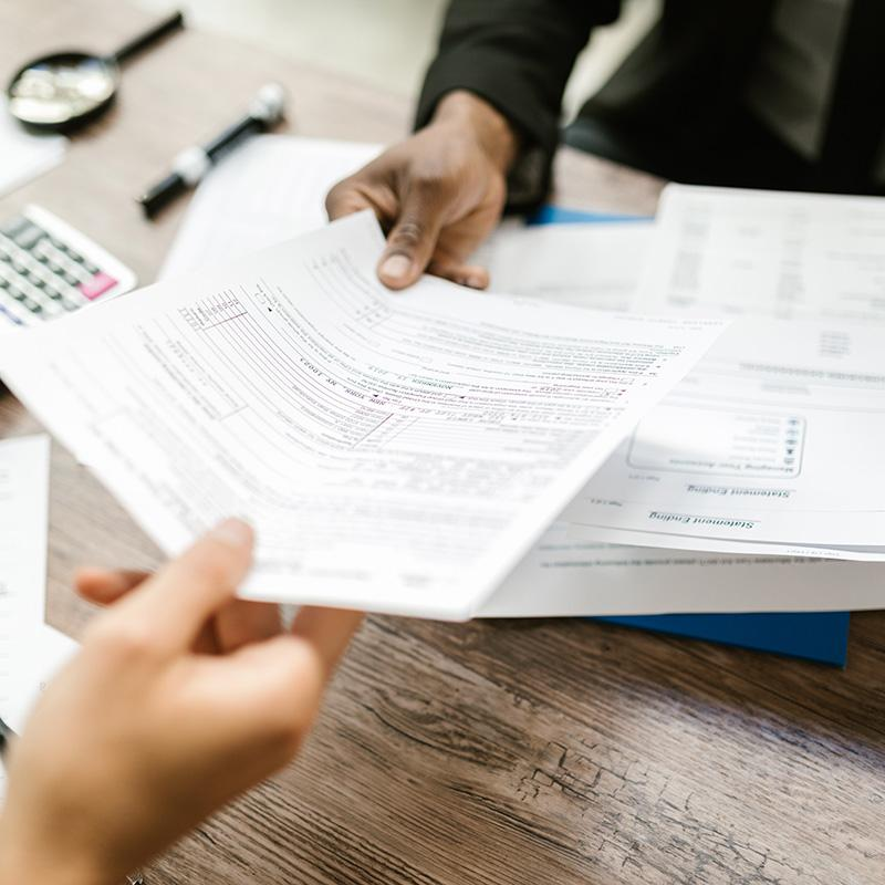 Photo is a closeup of a hand passing a tax document to another person's hand.