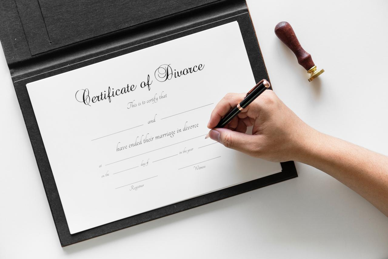 person writing on Certificate of Divorce